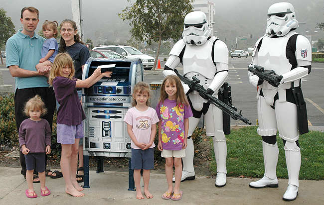 Alexis Gilbert joins two Storm Troopers at an R2-D2 collection box in San Diego. The Gilbert family heard about the collection boxes on the radio and, as huge fans, stopped by to take a photo and mail a letter -- the first letter mailed the morning of the installation.